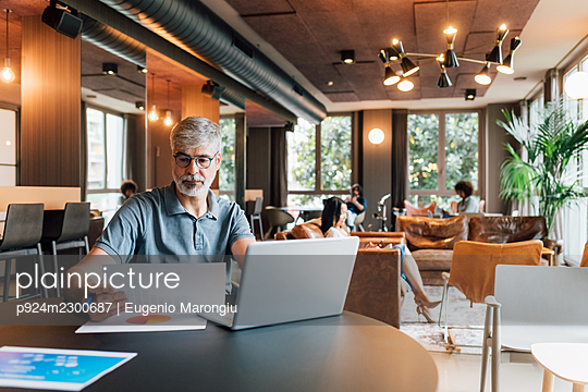 Italy, Businessman working at table in creative studio - p924m2300687 by Eugenio Marongiu