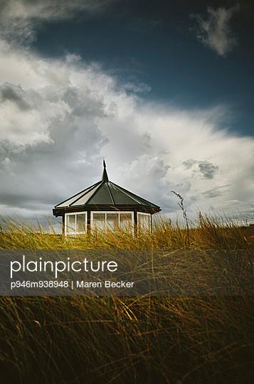 Gläserne Hütte mit spitzem Dach bei aufziehendem Sturm - p946m938948 von Maren Becker