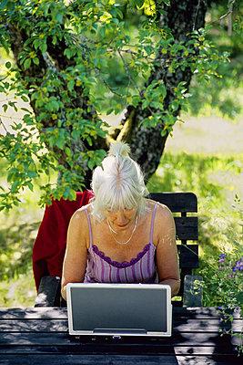 Ältere Frau arbeitet im Garten am Computer - p1418m1571288 von Jan Håkan Dahlström