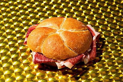 Serrano ham sandwich on a golden surface - p1423m2116657 von JUAN MOYANO