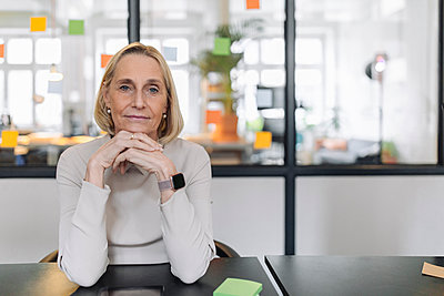 Portrait of confident mature businesswoman sitting at desk in office - p300m2156049 by Gustafsson