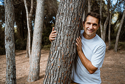 Smiling man embracing tree trunk in forest during vacation - p300m2241606 by Rafa Cortés