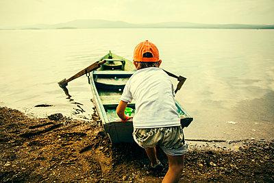 Caucasian boy pushing boat into still lake - p555m1418674 by Aliyev Alexei Sergeevich