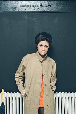 Female model in a beige rain-coat against a black background - p686m1124865 by Paul Tait