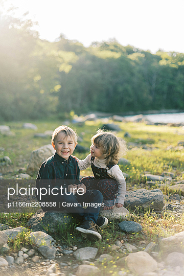 Two siblings whispering secrets to each other by the lake - p1166m2208558 by Cavan Images
