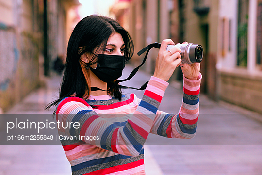 Young photographer with anti virus mask using her camera on a ci - p1166m2255848 by Cavan Images