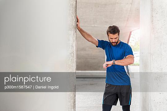 Man having a break from running checking the time - p300m1587547 von Daniel Ingold