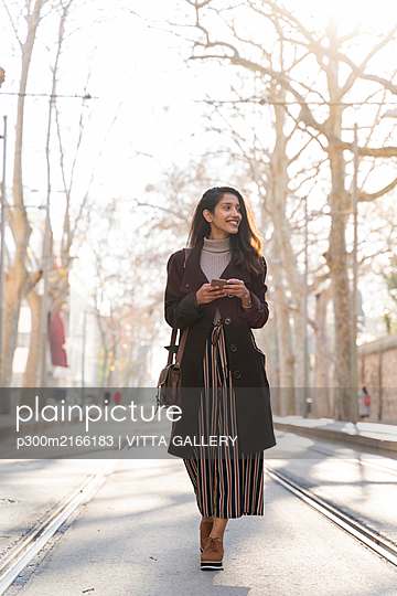 Smiling young woman with smartphone walking on tram line - p300m2166183 by VITTA GALLERY