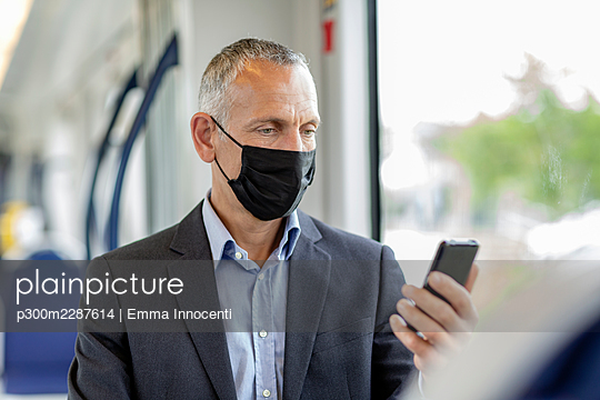 Male business professional using smart phone wearing protective face mask in tram during COVID-19 - p300m2287614 by Emma Innocenti
