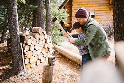 Father teaching son how to cut firewood outside cabin - p1192m2094144 by Hero Images