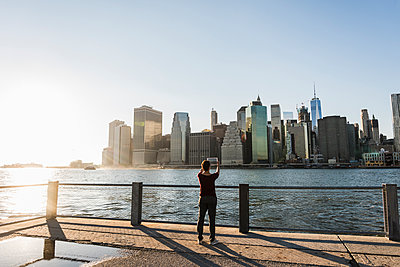 USA, Brooklyn, back view of woman taking picture of Manhattan skyline with tablet - p300m1205202 by Uwe Umstätter