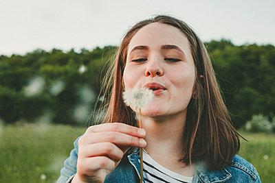 Portrait of teenage girl blowing blowball - p300m2114004 von Annie Hall