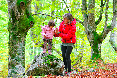 Mother holding hand of daughter standing on rock in Gorbea Natural park - p300m2274383 by David Santiago Garcia
