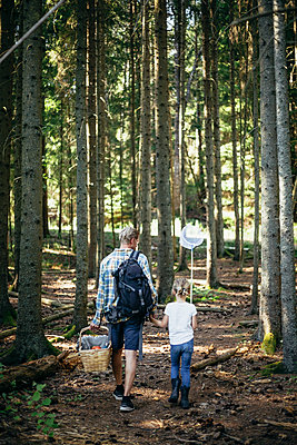 Rear view of father holding picnic basket while daughter with fishing net walking in forest - p426m2212157 by Maskot