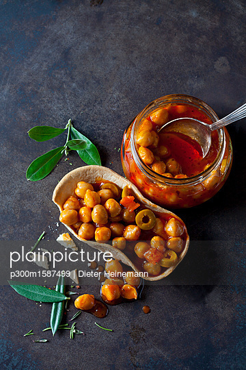 Chick-pea stew with green olives in glass and edible bowl - p300m1587499 von Dieter Heinemann
