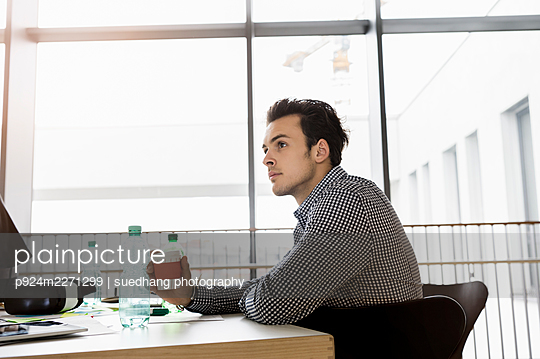 Germany, Bavaria, Munich, Young man sitting at desk in office - p924m2271299 by suedhang photography
