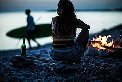 A group of young people gathered on a beach around a campfire. - p1100m1482337 by Mint Images