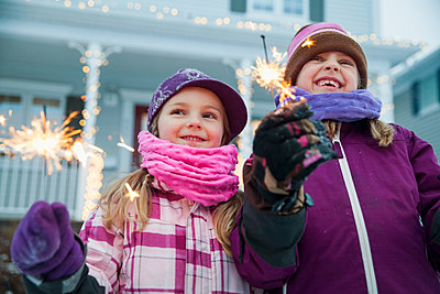 Girls standing outside with sparklers - p1192m1219280 by Hero Images