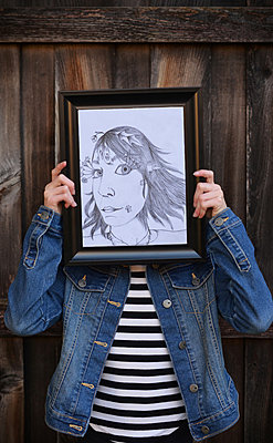 Girl Holding Self Portrait Drawing in Front of Face - p1617m2192187 by Barb McKinney