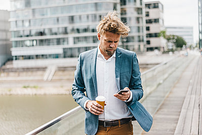Businessman with cell phone and coffee to go on bridge - p300m1175669 by Kniel Synnatzschke