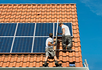 Workers installing solar panels on roof framework of new home, Netherlands - p429m954554f by Mischa Keijser