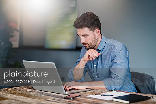 Mid adult male entrepreneur working on laptop over table in office - p300m2274229 by Daniel Ingold