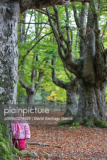 Cute girl smiling while standing by tree in Gorbea Natural Park - p300m2274429 by David Santiago Garcia