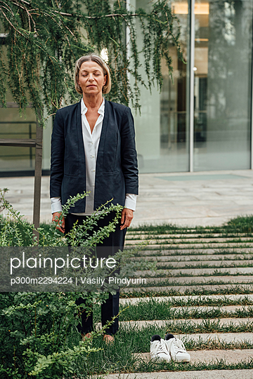 Mature businesswoman with eyes closed standing on footpath - p300m2294224 by Vasily Pindyurin