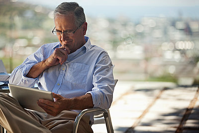 Older man using tablet computer outdoors - p1023m1146338 by Sam Edwards