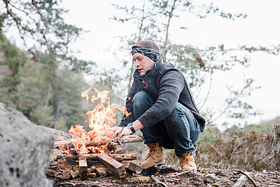 man putting sticks on a campfire outdoors in Sweden - p1166m2179462 by Cavan Images