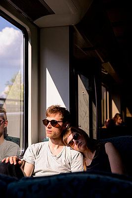 Junges Paar in der lichtdurchfluteten Bahn - einschlafen - p1212m1138831 von harry + lidy