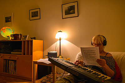 Woman playing keyboard and reading musical notes - p1418m2008120 by Jan Håkan Dahlström