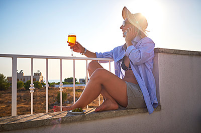 Woman with glass of spritz on cell phone on balcony - p300m1505256 by Dirk Kittelberger
