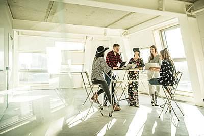Group of creative professionals having a meeting in a bright office, discussing new solutions - p300m2104282 by Malte Jäger