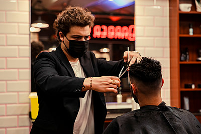 Barber with protective face mask cutting hair of customer in shop - p300m2287106 by Aitor Carrera Porté