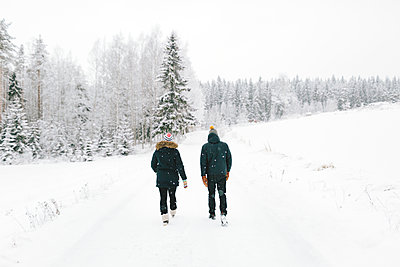 Finland, Jyvaskyla, Saakoski, Young couple walking along road covered with snow - p352m1141638 by Eija Huhtikorpi