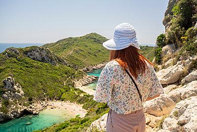 Tourist enjoying view on cliff top, Porto Timoni beach, Corfu, Kerkira, Greece - p429m2075462 by Tamboly