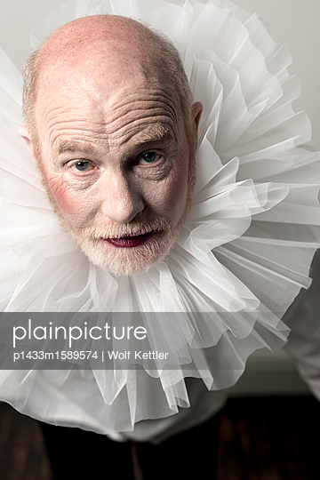Older man in Elizabethan theatrical makeup and frilly lace collar. - p1433m1589574 by Wolf Kettler