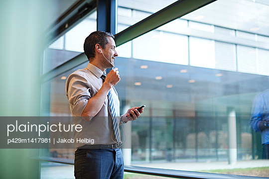 Mature businessman making telephone call while looking through office window - p429m1417981 by Jakob Helbig