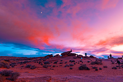 People climbing rock in evening under orange and pink sunset in Arizon - p1166m2137263 by Cavan Images