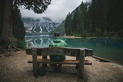 Italy, Man sitting on bench looking at Pragser Wildsee - p1427m2202258 by Oleksii Karamanov