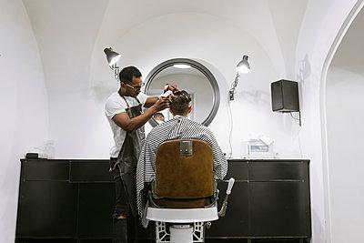 Barber cutting hair of a customer in barber shop - p300m2113907 von Hernandez and Sorokina