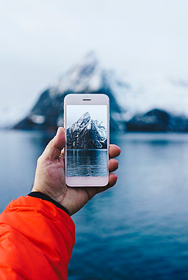 Close-up of tourist taking a smartphone picture at Hamnoy, Lofoten, Norway - p300m2166472 von Daniel González