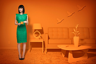Caucasian woman in orange old-fashioned livingroom drinking coffee - p555m1304582 by Chris Clor