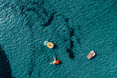 Three women on air mattress in the sea, drone photography - p713m2289222 by Florian Kresse