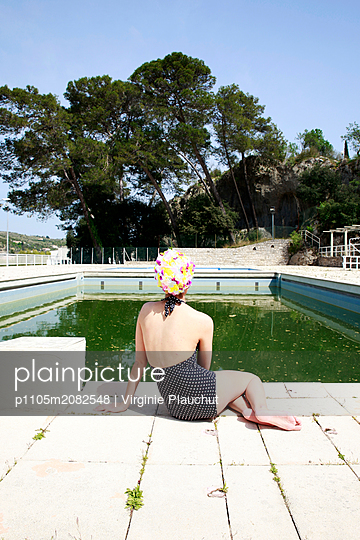 Woman sitting at the edge of outdoor pool, rear view - p1105m2082548 by Virginie Plauchut