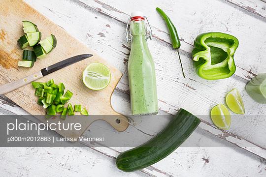 Glass bottle of homemade green Gazpacho and ingredients - p300m2012863 von Larissa Veronesi