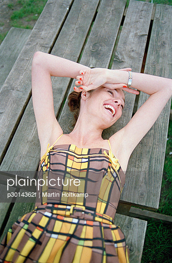 A woman lying on a picnic table, laughing