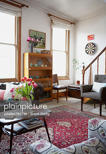 Red tulips in entrance room with red patterned rug - p349m789736 by Brent Darby