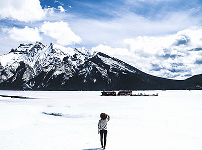 Rear view of woman looking at view while standing by frozen Lake Minnewanka against cloudy sky - p1166m1488880 by Cavan Images